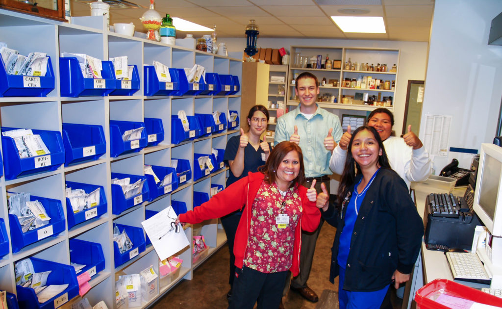 Pharmacist and pharmacy technicians working behind the pharmacy counter.