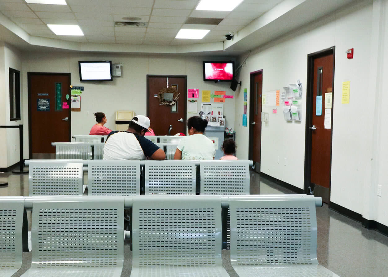 Patients in the waiting room filling out their financial assistance paperwork.